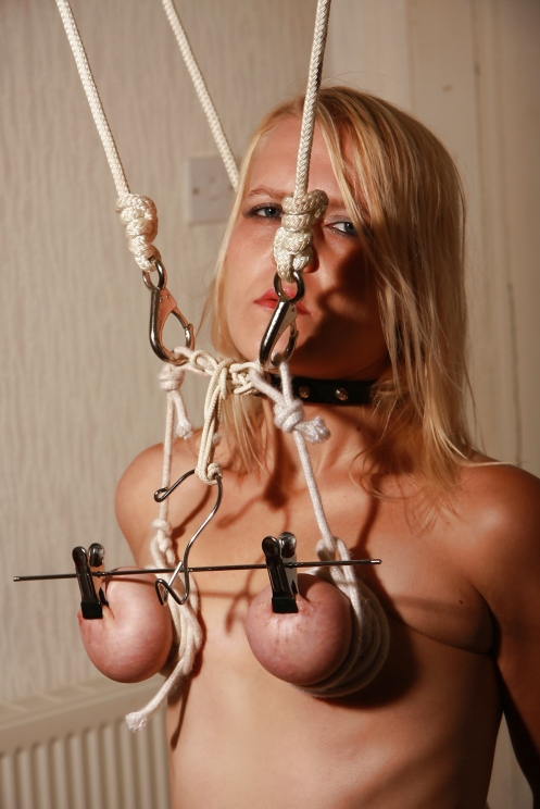 pulling her bound breasts by the nipples with a clothes hanger